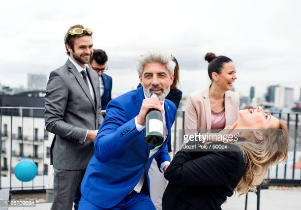 a group of joyful businesspeople having a party outdoors on roof terrace in city - big mike stock pictures, royalty-free photos & images