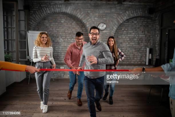 grupo de empresários alegres se divertindo em uma corrida de esportes no escritório - linha de chegada - fotografias e filmes do acervo