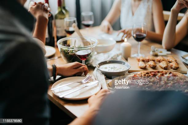 group of joyful young asian man and woman having fun, enjoying food and wine across table during party - cafe stock pictures, royalty-free photos & images