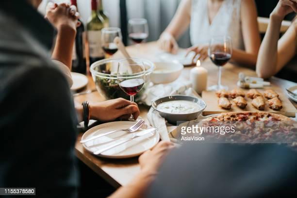 gruppe von fröhlichen jungen asiatischen mann und frau spaßen, genießen essen und wein über den tisch während der party - restaurant stock-fotos und bilder