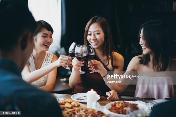 パーティー中に赤ワインで楽しく乾杯する喜びに満ちたアジアの若い女性のグループ - 東洋文化 ストックフォトと画像