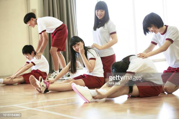 group of jr. high students making exercise in gymnastic hall - school gymnastics stock photos and pictures