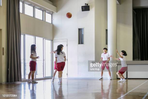 group of jr. high students making exercise in gymnastic hall - sports team event fotografías e imágenes de stock
