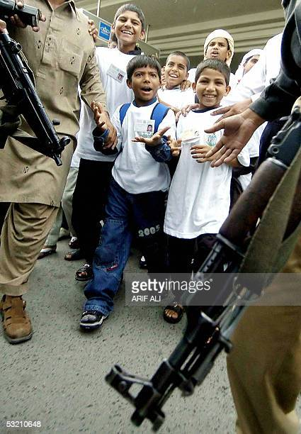 A group of jubilant Pakistani children who were smuggled and used as camel race jockeys in the United Arab Emirates are escorted by security...