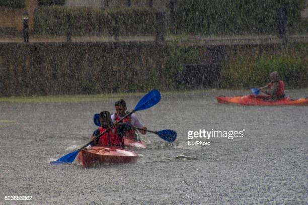 A group of kayakers sail under the heavy rain rain on the Regent's Canal London on July 27 2017 Torrential rain is typical in summer and the risk of...