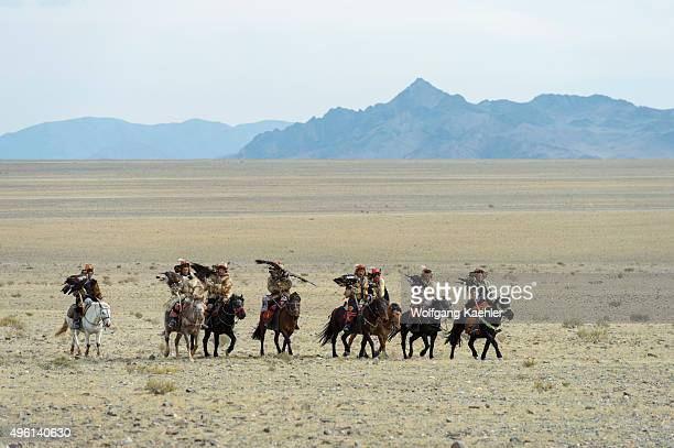 A group of Kazakh Eagle hunters and their Golden eagles arriving at the Golden Eagle Festival grounds near the city of Ulgii in the BayanUlgii...