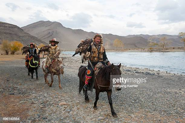 A group of Kazakh Eagle hunters and their Golden eagles on horseback at the Hovd River near the city of Ulgii in the BayanUlgii Province in western...
