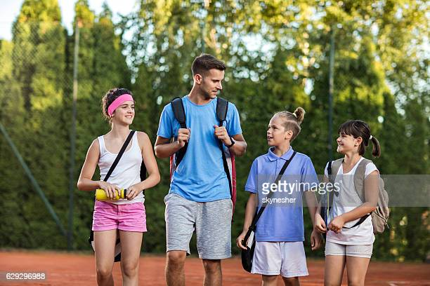 Group of kids and tennis trainer talking after the training.