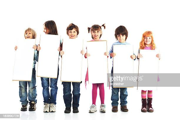 Group of kids are holding white boards for advertisements.