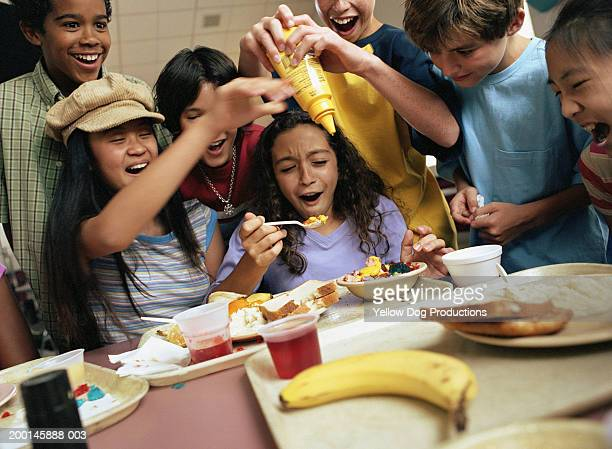 group of kids (12-14)        around table, boy pouring mustard in food - dog eats out girl stock pictures, royalty-free photos & images