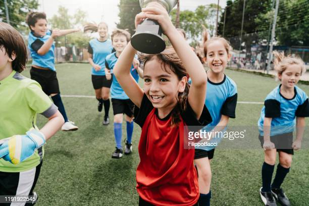 group of kids celebrating together the winning of a competition running on a soccer field - football team stock pictures, royalty-free photos & images