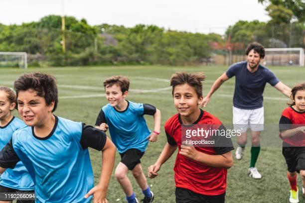 groep kinderen viert samen het winnen van een wedstrijd die op een voetbalveld loopt - 10 11 jaar stockfoto's en -beelden