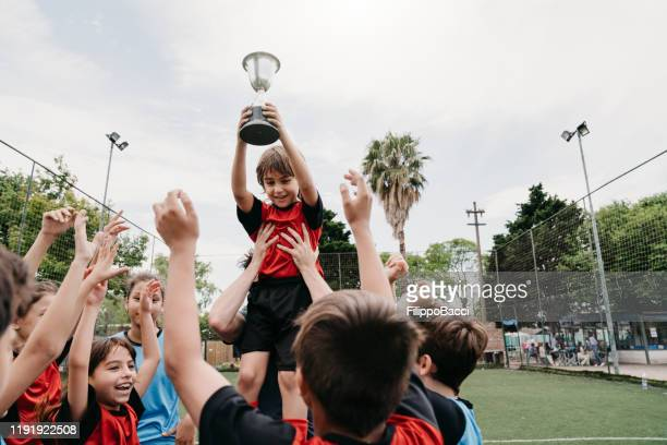 group of kids celebrating together with the coach the winning of a competition on a soccer field - soccer competition stock pictures, royalty-free photos & images