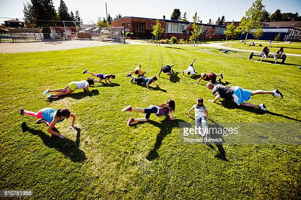 Group of kids doing leg lifts in athletics class