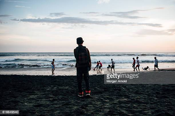 A group of kids from a rural village in Nicaragua play a game of football on the beach while the sun goes down