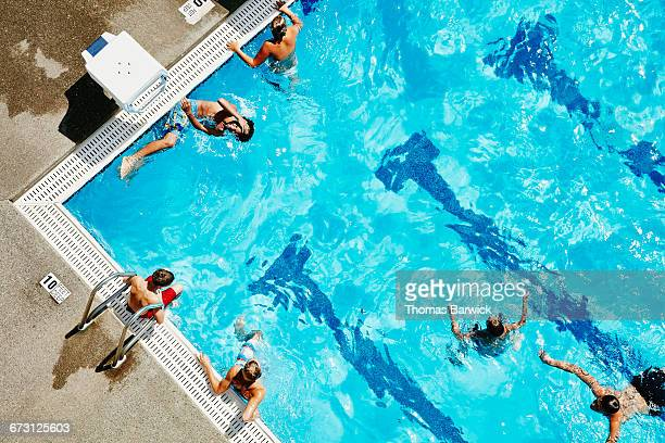 group of kids hanging out and playing in pool - riva dell'acqua foto e immagini stock