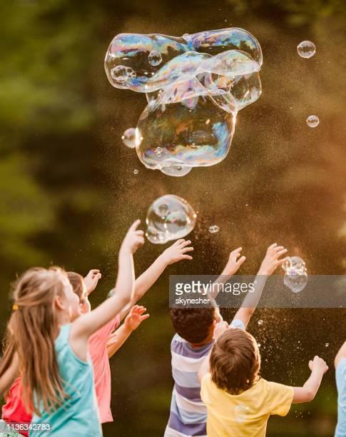 gruppe von kindern, die spaß am spielen mit regenbogenblasen im park haben. - interaktivität stock-fotos und bilder