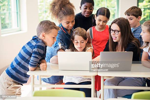 Group of kids learning to code in elementary school class.