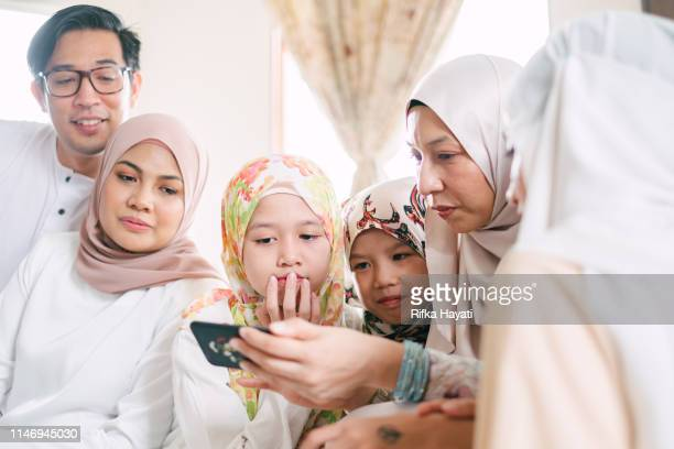 group of kids looking at mobile phone - eid ul fitr photos stock pictures, royalty-free photos & images