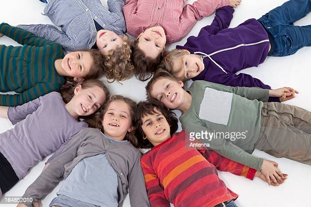 A group of kids lying on their backs in a circle, heads touching