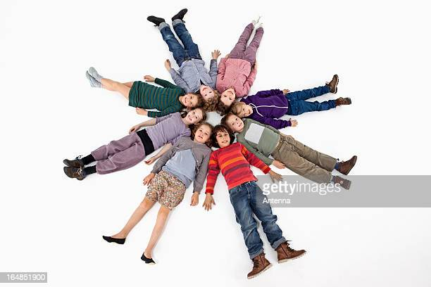 A group of kids lying on their backs in a circle