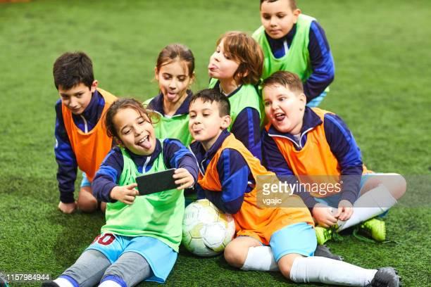 groep van kinderen maken selfie na voetbal training - sports uniform stockfoto's en -beelden