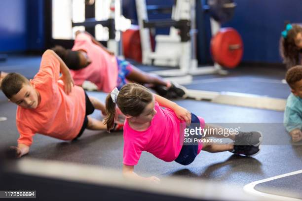 group of kids performing side planks during fitness class - physical education stock pictures, royalty-free photos & images