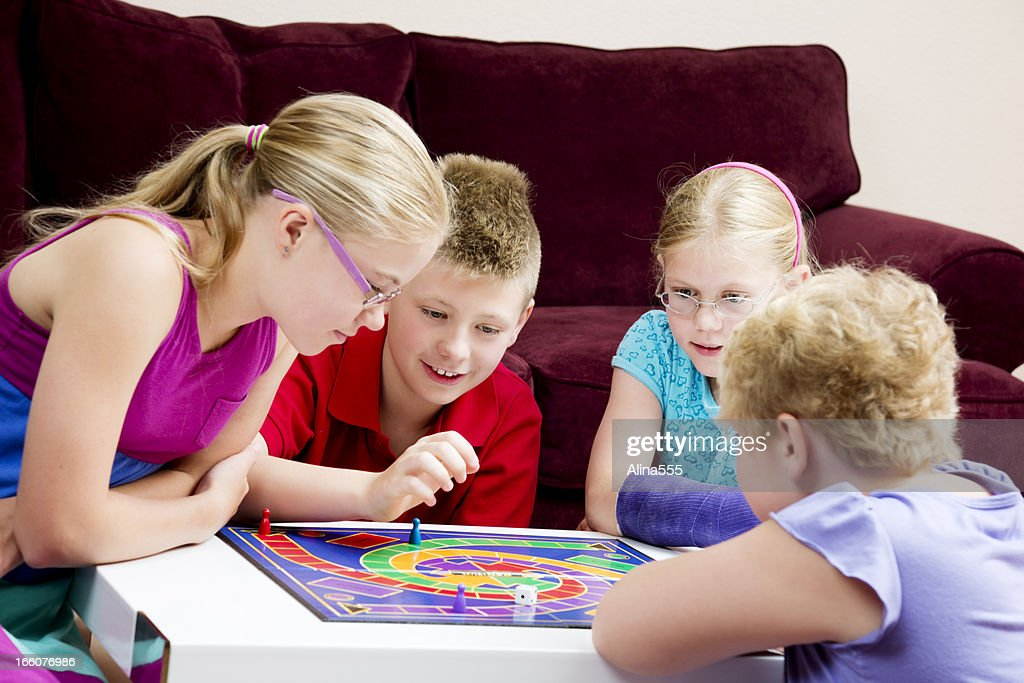 Group of kids playing board game in a living room : Stock Photo