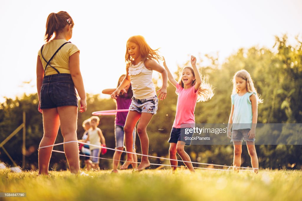 Group of kids playing outdoors jumping the ruber band : Stock Photo