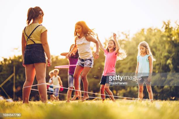 group of kids playing outdoors jumping the ruber band - skipping rope stock pictures, royalty-free photos & images