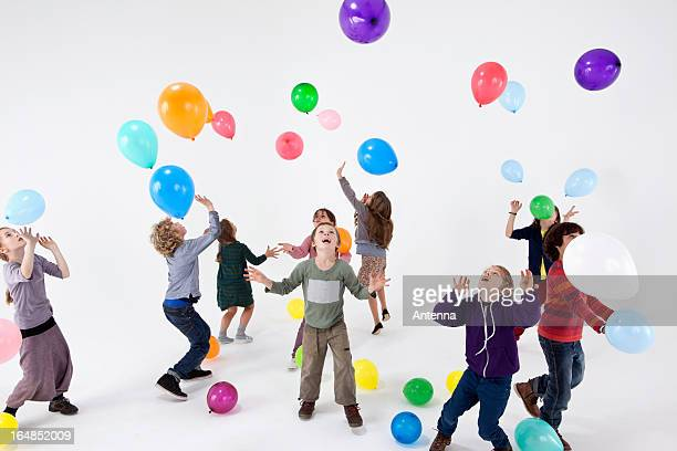 A group of kids playing with balloons