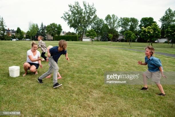 Gruppe der Kinder mit Wasser spielen reichte Ballon im Vorort Park.