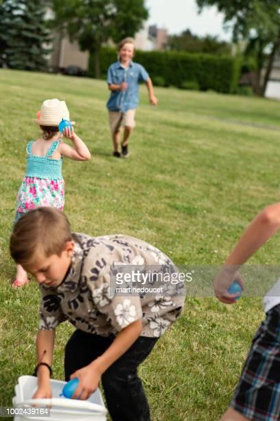 Gruppe von Kindern beim Spielen mit Wasser gefüllten Ballons im Vorort Park.