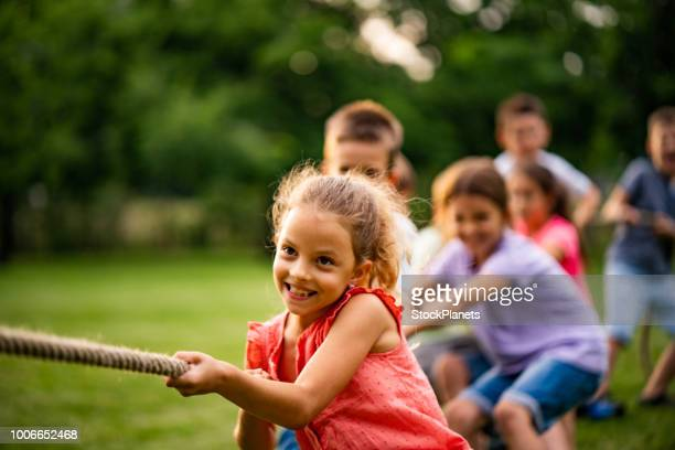 group of kids pulling a rope - strength stock pictures, royalty-free photos & images