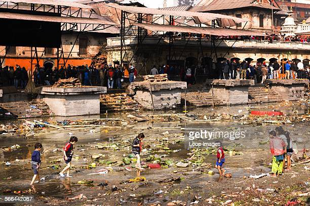 A group of kids scavenging for valuables amongst the debris of the offerings left in the river at Pashupatinath Temple in Kathmandu