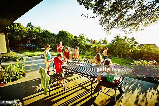 Group of kids sitting on patio eating hot dogs