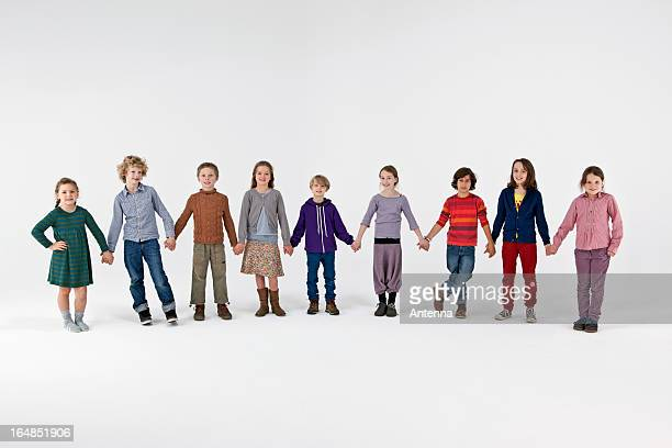 A group of kids standing in a row and holding hands
