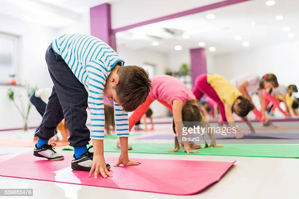group of kids stretching their legs on a sports training. - gymnastiek stockfoto's en -beelden