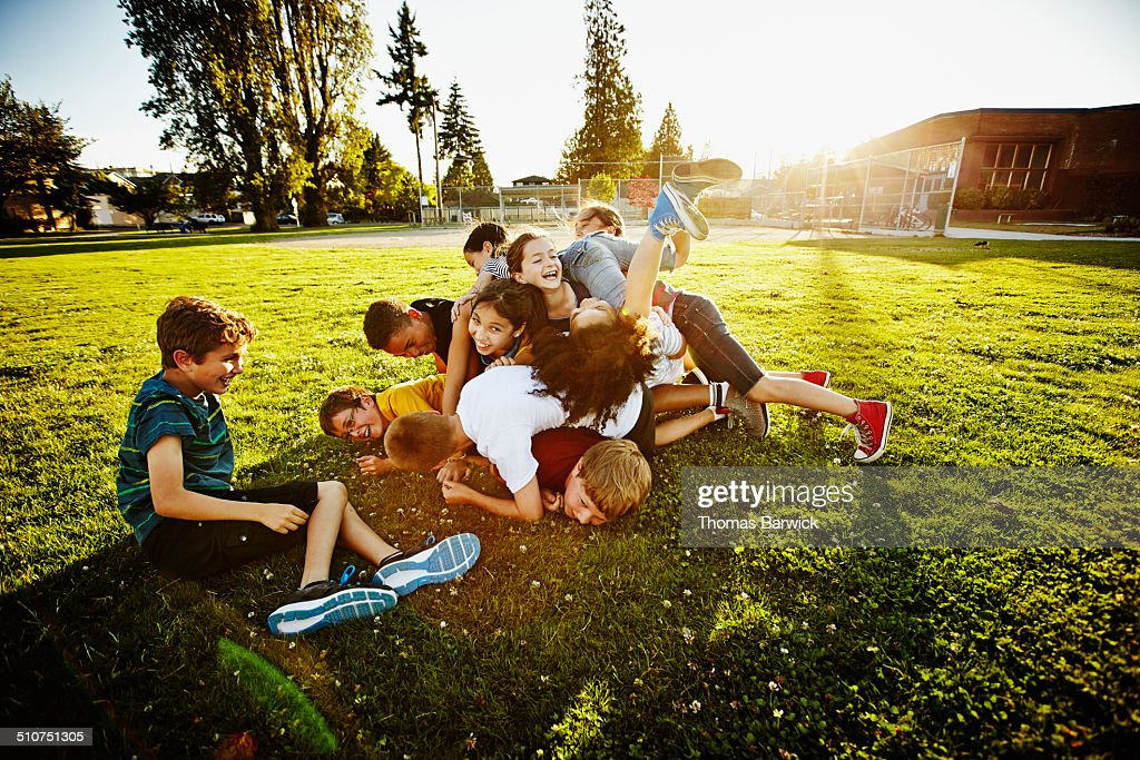 Group of kids tackling and piling on each other : Stock Photo