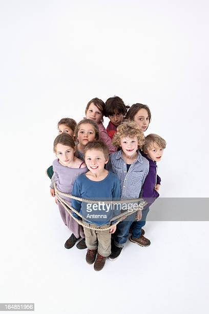 a group of kids tied together with a rope - restraining stock photos and pictures
