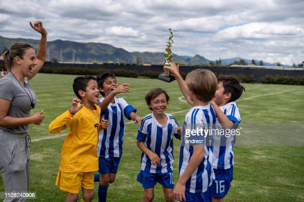 group of kids winning a trophy playing soccer - sports training camp stock pictures, royalty-free photos & images