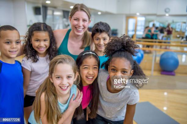 group of kids with gym teacher - pe teacher stock photos and pictures