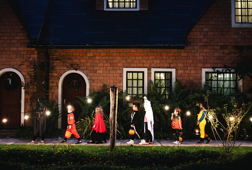 Group of kids with Halloween costumes walking to trick or treating 1038570816