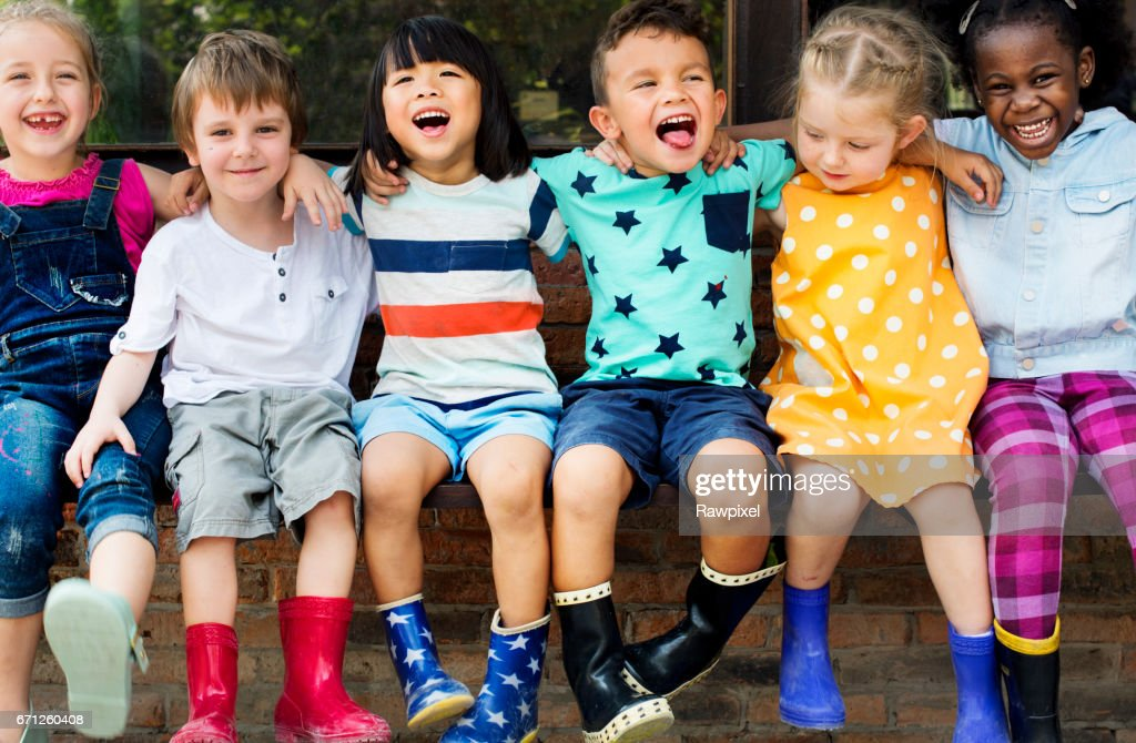 Group of kindergarten kids friends arm around sitting and smiling fun : Stock Photo