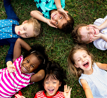 Group of kindergarten kids lying on the grass at park and relax with smiling 671260158