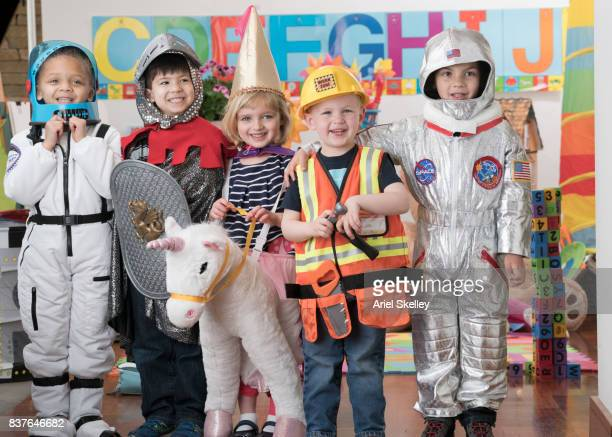 Group of kindergarteners playing dress up in classroom