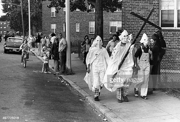 A group of Ku Klux Klan impersonators carry a large cross as they walk past the Old Colony housing project on Columbia Road in Boston on Sept 18 1974...