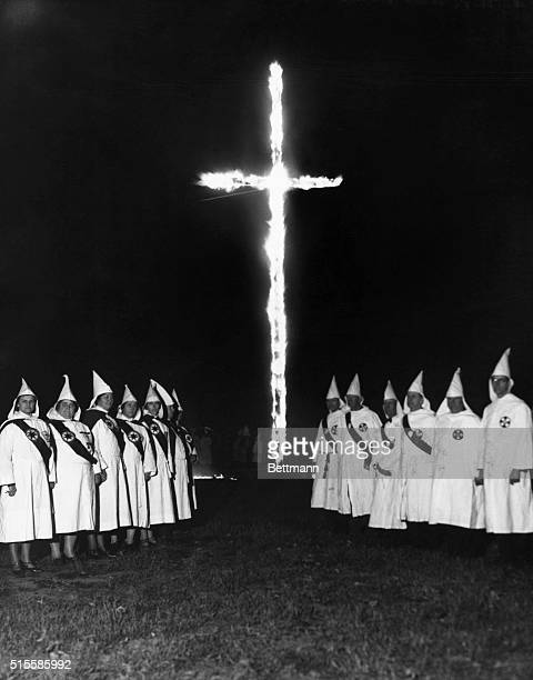 A group of Ku Klux Klan men and women in typical Klan attire around the burning cross Undated photograph