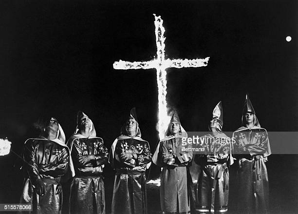 A group of Ku Klux Klansman wearing their robes stand in front of a burning cross at Stone Mountain Georgia