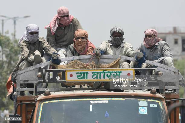 Group of laborers sitting atop a truck cover their faces to avoid the heat at noon on a summer day, at Chattarpur, on June 9, 2019 in New Delhi,...